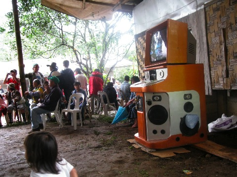 People surrounded around a videoke machine.